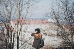 Αρκετά νέα γυναίκα στην τοποθέτηση καπέλων με τα λουλούδια στην τσάντα Στοκ Εικόνες