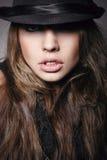 Αρκετά νέα γυναίκα στο μαύρο καπέλο που εξετάζει τη κάμερα Στοκ Φωτογραφίες