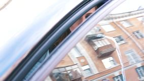 Αρκετά νέα γυναίκα στο μαύρο σακάκι που βγαίνει από το σκοτεινό αυτοκίνητό της στην οδό στην ηλιόλουστη ημέρα άνοιξη r E απόθεμα βίντεο