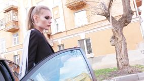 Αρκετά νέα γυναίκα στο μαύρο σακάκι, τα μαύρα ψηλοτάκουνα παπούτσια και τα εσώρουχα capri που βγαίνουν από το μαύρο αυτοκίνητο πο φιλμ μικρού μήκους