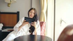 Αρκετά νέα γυναίκα στο μπουρνούζι που κουβεντιάζει στη συνεδρίαση υπολογιστών ταμπλετών στην καρέκλα στο δωμάτιο ξενοδοχείου φιλμ μικρού μήκους