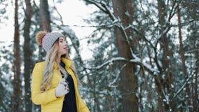 Αρκετά νέα γυναίκα τρεξίματα στα κίτρινα σακακιών γύρω από ένα χειμερινό δάσος φιλμ μικρού μήκους