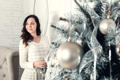 Αρκετά νέα γυναίκα brunette που στέκεται κοντά στο δέντρο έλατου στα Χριστούγεννα Στοκ φωτογραφίες με δικαίωμα ελεύθερης χρήσης