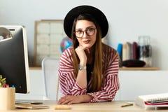 Αρκετά νέα επιχειρησιακή γυναίκα που εξετάζει τη κάμερα στο γραφείο Στοκ Φωτογραφία