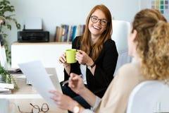 Αρκετά νέα επιχειρησιακή δύο γυναίκα που χαλαρώνει μια στιγμή πίνοντας τον καφέ στο γραφείο στοκ φωτογραφία με δικαίωμα ελεύθερης χρήσης