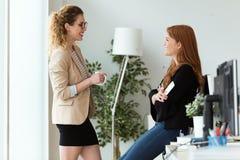 Αρκετά νέα επιχειρησιακή δύο γυναίκα που χαλαρώνει μια στιγμή πίνοντας τον καφέ στο γραφείο στοκ φωτογραφίες