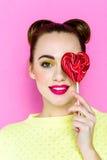 Αρκετά νέα εύθυμη εκμετάλλευση κοριτσιών καρδιά-που διαμορφώνεται lollipop Στοκ Φωτογραφίες