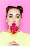 Αρκετά νέα εύθυμη εκμετάλλευση κοριτσιών καρδιά-που διαμορφώνεται lollipop Στοκ Εικόνες