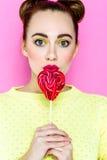 Αρκετά νέα εύθυμη εκμετάλλευση κοριτσιών καρδιά-που διαμορφώνεται lollipop Στοκ εικόνες με δικαίωμα ελεύθερης χρήσης