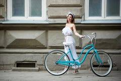 Αρκετά νέα θηλυκή τοποθέτηση με το μπλε ποδήλατο μπροστά από το παλαιό ιστορικό κτήριο στοκ φωτογραφίες