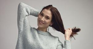 Αρκετά νέα ισπανική τοποθέτηση γυναικών στο studia που εξετάζει τη κάμερα και χαμόγελο Στοκ Εικόνες