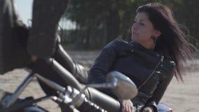 Αρκετά νέα καυκάσια γυναίκα σε ένα μαύρο σακάκι και τα εσώρουχα δέρματος που βρίσκονται σε μια κλασική μοτοσικλέτα Χόμπι, που ταξ απόθεμα βίντεο