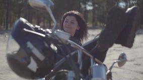 Αρκετά νέα καυκάσια γυναίκα σε ένα μαύρο σακάκι και τα εσώρουχα δέρματος που βρίσκονται σε μια μοτοσικλέτα Χόμπι, που ταξιδεύει κ απόθεμα βίντεο