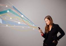 Αρκετά νέα κυρία που κρατά ένα τηλέφωνο με τις ζωηρόχρωμες αφηρημένες γραμμές α Στοκ εικόνες με δικαίωμα ελεύθερης χρήσης