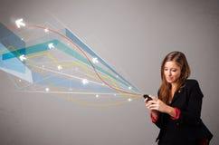 Αρκετά νέα κυρία που κρατά ένα τηλέφωνο με τις ζωηρόχρωμες αφηρημένες γραμμές α Στοκ εικόνα με δικαίωμα ελεύθερης χρήσης