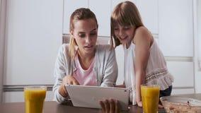 Αρκετά νέα μητέρα και η κόρη της που χρησιμοποιούν την ψηφιακή ταμπλέτα ενώ έχοντας το πρόγευμα στην κουζίνα στο σπίτι