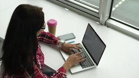 Αρκετά νέα μικτή γυναίκα φυλών hipster που εργάζεται στο lap-top απόθεμα βίντεο