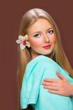 Αρκετά νέα ξανθή γυναίκα με την όμορφη τρίχα, την μπλε πετσέτα και το ΛΦ Στοκ Φωτογραφία