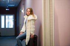 Αρκετά νέα ξανθή γυναίκα που ταξιδεύει φορώντας ένα παλτό, τζιν που τραβά μια βαλίτσα στοκ εικόνα με δικαίωμα ελεύθερης χρήσης