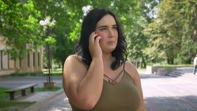 Αρκετά νέα παχύσαρκη γυναίκα που μιλούν στο τηλέφωνο κυττάρων και χαμόγελο, που στέκεται στην οδό στο πάρκο, ευτυχής και εύθυμος φιλμ μικρού μήκους