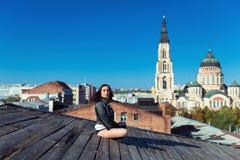Αρκετά νέα προκλητική συνεδρίαση γυναικών στην ξύλινη στέγη Στοκ Φωτογραφία