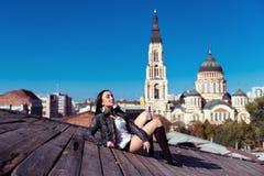 Αρκετά νέα προκλητική συνεδρίαση γυναικών στην ξύλινη στέγη Στοκ Εικόνες
