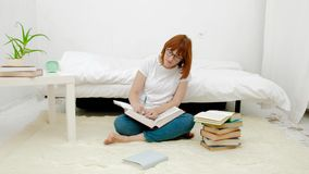 Αρκετά νέα συνεδρίαση γυναικών στο πάτωμα καθιστικών της που αυτοσχεδιάζει χρησιμοποιώντας τους υψηλούς σωρούς των βιβλίων φιλμ μικρού μήκους