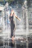 Αρκετά νέα χαλάρωση γυναικών στην πηγή οδών το καυτό καλοκαίρι DA Στοκ Εικόνες