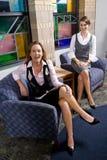 Αρκετά νέες γυναίκες που κάθονται στην έδρα αίθουσας αναμονής στοκ εικόνες