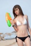 Αρκετά νέες γυναίκες που παίζουν με το πυροβόλο όπλο νερού στην παραλία Στοκ φωτογραφία με δικαίωμα ελεύθερης χρήσης