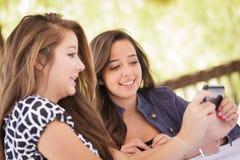 Αρκετά νέες φίλες εφήβων που χρησιμοποιούν το έξυπνο τηλέφωνό τους στοκ εικόνα