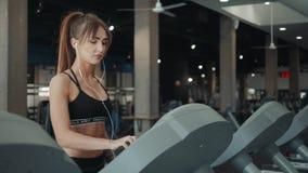 Αρκετά νέος αθλητής γυναικών με το smartphone που τρέχει treadmill στη γυμναστική, μουσική ακούσματος κοριτσιών γυναικών στο κινη απόθεμα βίντεο