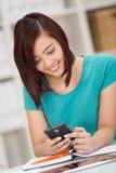 Αρκετά νέος ασιατικός σπουδαστής που διαβάζει ένα μήνυμα κειμένου στοκ εικόνες