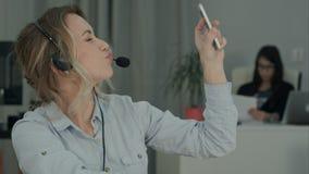 Αρκετά νέος εργαζόμενος γραφείων στην κάσκα που παίρνει τα αστεία selfies στον εργασιακό χώρο στοκ εικόνες