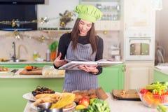 Αρκετά νέος θηλυκός μάγειρας που φορά το καπέλο αρχιμαγείρων s που ψάχνει μια συνταγή στο cookbook που στέκεται στην κουζίνα στοκ εικόνες με δικαίωμα ελεύθερης χρήσης