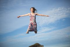 Αρκετά νέος θηλυκός μπλε ουρανός υποβάθρου άλματος στοκ εικόνες
