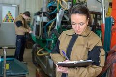 Αρκετά νέος μηχανικός γυναικών που ελέγχει για τις δυσλειτουργίες στο εργοστάσιο στοκ εικόνα