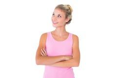 Αρκετά νέος ξανθός στο ροζ που ανατρέχει με τα όπλα που διασχίζονται Στοκ Φωτογραφία