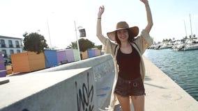 Αρκετά νέος χαμογελώντας τουρίστας γυναικών που περπατά και που απολαμβάνει την ηλιόλουστη θερινή ημέρα φιλμ μικρού μήκους