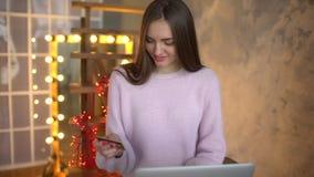 Αρκετά νέο έφηβη που ψωνίζει on-line χρησιμοποιώντας την πιστωτική κάρτα και το φορητό προσωπικό υπολογιστή της 4 Κ Γυναίκα που κ απόθεμα βίντεο