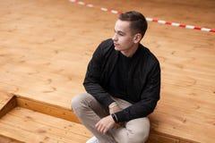 Αρκετά νέο ελκυστικό μοντέρνο άτομο σε ένα μοντέρνο μαύρο σακάκι άνοιξη στο μπεζ παντελόνι στα πάνινα παπούτσια που θέτουν τη συν στοκ εικόνες με δικαίωμα ελεύθερης χρήσης