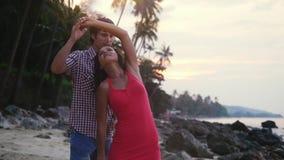 Αρκετά νέο ζεύγος που χορεύει ένας αργός χορός στην τροπική παραλία στο χρόνο ηλιοβασιλέματος κίνηση αργή 1920x1080 απόθεμα βίντεο