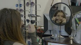 Αρκετά νέο κορίτσι εφήβων που δοκιμάζει τα διάφορα εμπορικά σήματα των γυαλιών ηλίου σε ένα κατάστημα - φιλμ μικρού μήκους