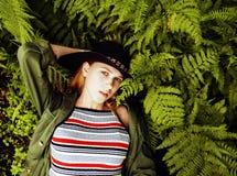 Αρκετά νέο ξανθό κορίτσι hipster στο καπέλο μεταξύ της φτέρης, διακοπές στο πράσινο δάσος, έννοια ανθρώπων μόδας τρόπου ζωής Στοκ εικόνες με δικαίωμα ελεύθερης χρήσης