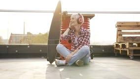 Αρκετά νέο χαμογελώντας hipster κορίτσι στο αστικό υπόβαθρο που ακούει τη μουσική με τα ακουστικά Αρκετά νέο χαμόγελο ξανθό απόθεμα βίντεο