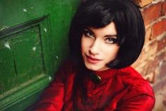 Αρκετά νέο brunette με την κοντή τρίχα σε ένα πράσινος-κόκκινο υπόβαθρο Στοκ φωτογραφία με δικαίωμα ελεύθερης χρήσης