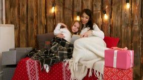 Αρκετά νέο mom που διαβάζει μια ιστορία Χριστουγέννων στη χαριτωμένη συνεδρίαση κορών της στον καναπέ που τυλίγεται στα καλύμματα φιλμ μικρού μήκους