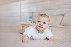 Αρκετά νεογέννητα ψέματα και χαμόγελα σε ένα κρεβάτι στο σπίτι Στοκ Φωτογραφία