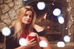 Αρκετά ξανθή γυναίκα κοντά στην εστία με το φλιτζάνι του καφέ με το έλος στοκ φωτογραφία