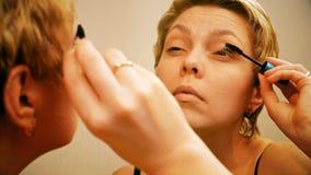 Αρκετά ξανθή γυναίκα που εφαρμόζει mascara τη σύνθεση φιλμ μικρού μήκους
